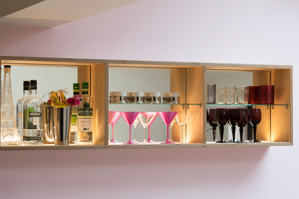 Contemporary bar cabinet. Hand crafted in birch plywood with glass shelves, mirror backs and LED up-lighting.