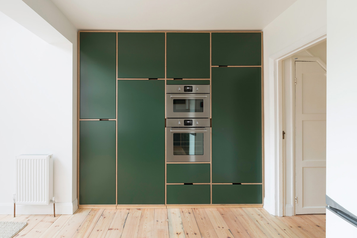 Bespoke floor to ceiling plywood kitchen cabinets with exposed frame cut out handles, inset doors and built in ovens.