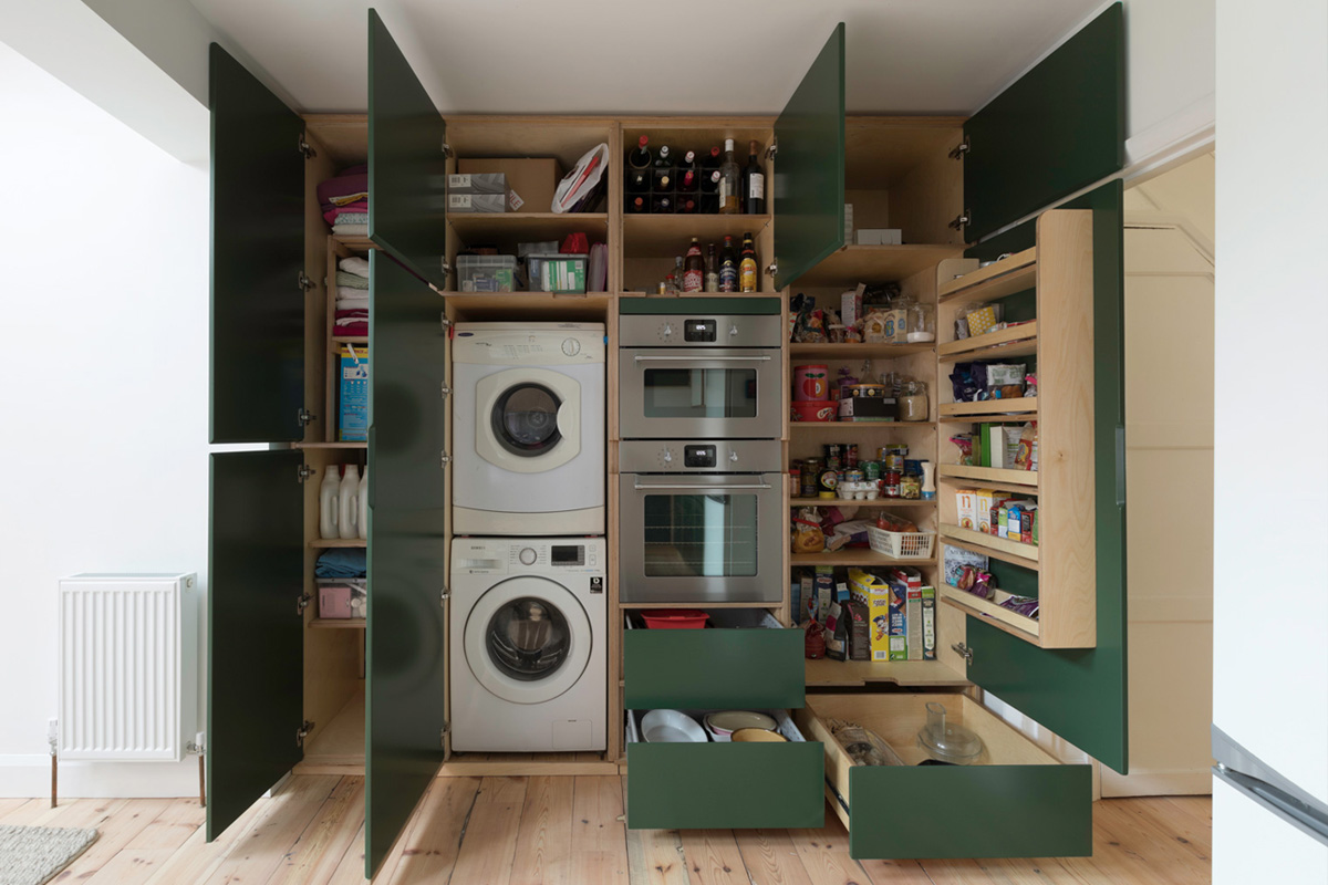 Tall fitted plywood cabinets with drawers showing modern internal storage - larder, washing machine, dryer and boiler cupboards.