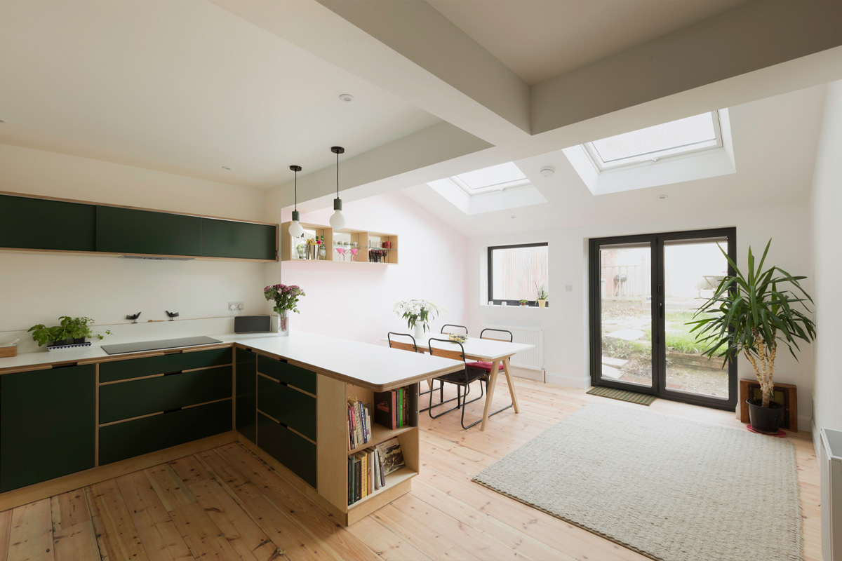 Open plan kitchen dining room with Velux windows and patio doors. Bespoke cabinets featuring bookcase and drinks cabinet.